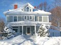 The front of a large older home covered in deep snow.
